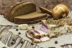Bacon salgado rústico com pão, cebolas e alho Imagens de Stock