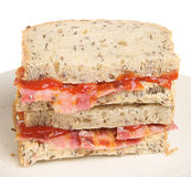 Bacon Sandwich. Crispy streaky bacon sandwich with tomato ketchup Royalty Free Stock Photos