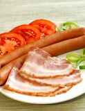 bacon, sausage and tomatoes on plate Royalty Free Stock Photography