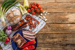 Bacon and sausage with vegetables. Bacon and sausage with fresh vegetables on a rustic brown wooden vintage table royalty free stock photos