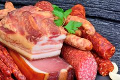 Bacon with sausages and prosciutto crudo and salami on a wood background. Close-up Stock Images