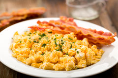 Bacon with scrambled eggs. Freshly fried bacon served with scrambled eggs and chives Stock Photos