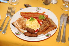 Bacon, Scrambled Eggs, Sausage, Toast - Breakfast. Traditional fried English breakfast of scrambled eggs, bacon, toast and sausages Stock Photos