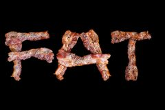 Bacon shaped as the word FAT on black background Royalty Free Stock Photography