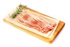 Bacon sistemato sul bordo di legno sopra bianco Immagine Stock Libera da Diritti