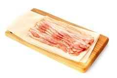 Bacon sistemato sul bordo di legno sopra bianco Immagini Stock Libere da Diritti