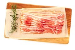 Bacon sistemato sul bordo di legno sopra bianco Fotografia Stock