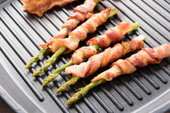 Bacon slice and asparagus wrapped in bacon being cooked in fryin. G pan Royalty Free Stock Photos