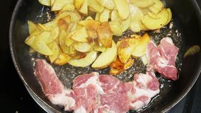 Bacon and sliced potatoes are fried in frying pan on stove stock footage