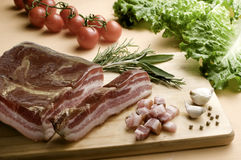Bacon. Slices and dice, on wooden table stock photos