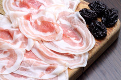 Bacon slices with prunes on wooden chopping board Stock Photo