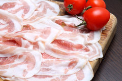 Bacon slices on wooden cutting board Stock Photo