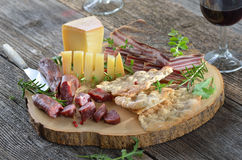 Bacon snack. Typical South Tyrolean snack with hearty cured bacon, mountain cheese, smoked sausages, crispy rye flatbread and a glass of red wine Royalty Free Stock Image