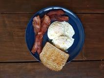 bacon, sobre o ovo fácil, e café da manhã inteiro brindado do pão integral Imagens de Stock