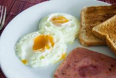 Bacon, stekte ägg och rostat bröd Arkivfoto