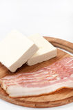 Bacon strips arranged on a kitchen board and white feta cheese Stock Image