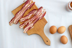 Bacon strips and eggs, making breakfast Royalty Free Stock Photos