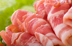 Bacon strips and lettuce. A closeup view of folded strips of bacon with green lettuce in the background Stock Image