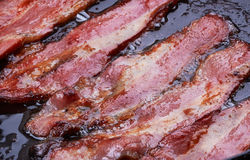 Bacon. Strips or rashers being cooked in frying pan Stock Photo