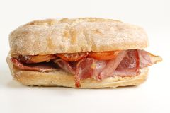 Bacon and tomato sandwich. Crispy grilled bacon and tomato on a crusty bread roll Stock Photography