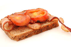 Bacon and tomatoes on bread Stock Images