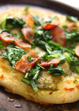 Bacon-topped pizza with greens Royalty Free Stock Photos