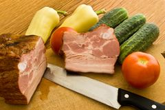 Bacon and vegetables. Smoked meat and vegetables on chopping board royalty free stock photos