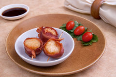 Bacon wrap scallops. Plate of three bacon wrapped scallops with cherry tomato garnish on a brown plate with sauce and napkin Stock Photography