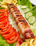 Bacon Wrap. Very ricj and long bacon wrapped kebab or dog served with plenty of vegetable salad Royalty Free Stock Images