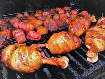 Bacon Wrapped Chicken Drumbsticks and Burnt Ends on the Grill royalty free stock photo