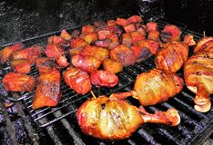 Bacon Wrapped Chicken Drumbsticks and Burnt Ends on the Grill royalty free stock photography
