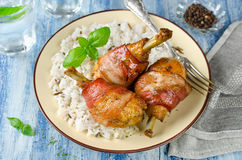 Bacon wrapped chicken legs with rice garnish Stock Image