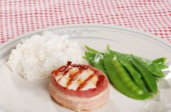 Bacon wrapped chicken with snow peas white rice Stock Image