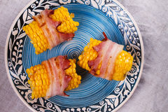 Bacon wrapped corn on blue plate. View from above, top studio shot Stock Photos