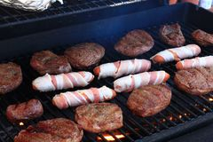 Bacon Wrapped hot dogs on a grill Royalty Free Stock Photo