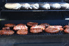 Bacon Wrapped hot dogs and steaks on a grill Stock Photography