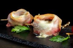 Bacon Wrapped Mushrooms Stuffed on black slate. stock photos