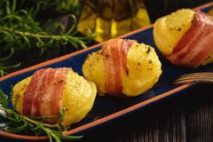 Bacon wrapped potatoes, baked with cheese. Stock Photos