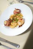Bacon wrapped scallops and Fettuccine royalty free stock images
