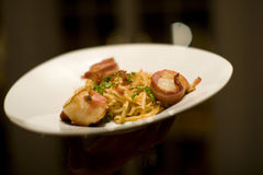 Bacon wrapped scallops and Fettuccine on a white plate royalty free stock image