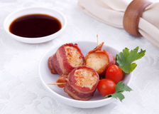 Bacon wrapped scallops and sauce. Plate of three bacon wrapped scallops with cherry tomato garnish on a brown plate with sauce and napkin Royalty Free Stock Images
