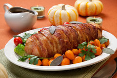 Bacon-wrapped Turkey Breast Roulade. Delicious bacon-wrapped turkey breast roulade garnished with Brussels sprouts, tomatoes, and Parisian carrots Royalty Free Stock Photography