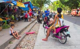 Bacong Filippinerna: 26 Juni, 2016: Stor familj på den rosa mopeden vid den lokala marknaden Royaltyfri Foto