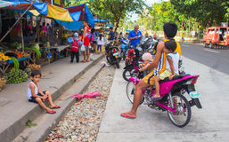Bacong, Philippines: 26 June, 2016: Big family on pink motorbike by local market. Asian food market with local people from village. Philippines poor children Royalty Free Stock Photo