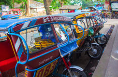 Bacong, Philippines - 26 June, 2016: Tricycle - public form of transport in the Philippines. Tuk-tuk or rickshaw colorful motorcycle with handmade passenger Royalty Free Stock Photos