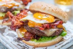 Baconhamburgare med ägggrönsallat och ost royaltyfri bild