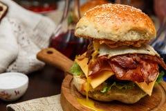 Baconhamburger met rundvleespasteitje en ei op houten lijst Stock Afbeelding