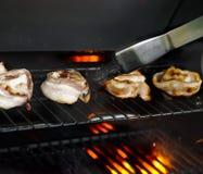 Baconkammussla på flammagallerbbq arkivfoton