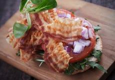 Baconsmörgås med tomat- och raketsallad Fotografering för Bildbyråer