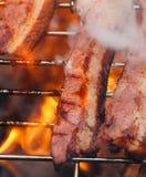 Baconvlees bij bbq de barbecuegrill met brand Royalty-vrije Stock Afbeeldingen